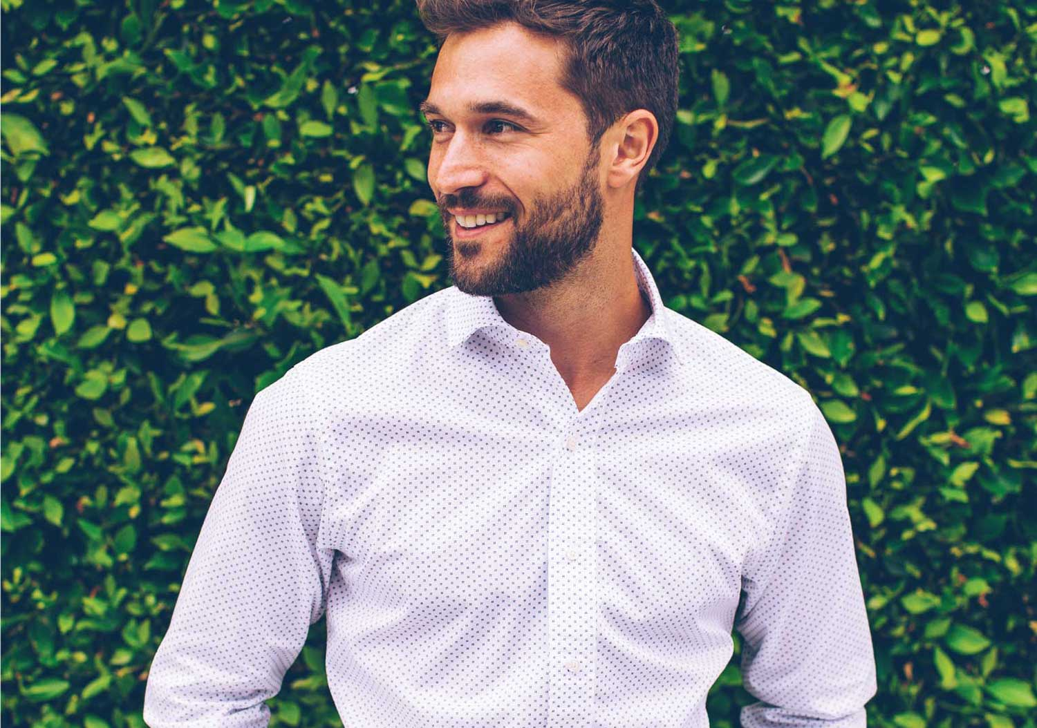 Man wearing Ratio Clothing shirt in front of hedges